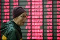 An investor smiles as he checks his stocks on a day when the market rises in reaction to the regulator's move on mutual funds. Photo: AP