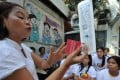 A Philippine health worker holding samples of contraceptives during a lecture to pregnant women on responsible family planning. Photo: AFP