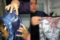 A mother shows a slashed coat hood and a father displays a bloody shirt in explaining how their sons were hurt in a knife attack. Photos: AFP