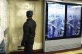 """A man looks at a poster for Hollywood disaster movie """"2012"""" at a subway station in Beijing. Photo: AFP"""