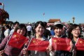 Visitors with the national flags in hands pose for photos on the Tian'anmen Square. Photo:Xinhua
