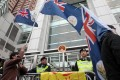 Protesters display Hong Kong colonial flags outside the liaison office on Tuesday. Photo: SCMP