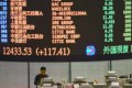 A trader walks the floor of the Hong Kong Stock Exchange as share prices are flashed. Photo: AFP
