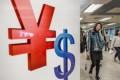 A woman walks past Chinese yuan (L) and US dollars symbols in Hong Kong. Photo: AFP