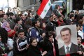 Demonstrators march in support of President Bashar al-Assad in Homs, Syria, on Sunday. Photo: AFP