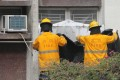 Firefighters cover windows of the woman's flat. Photo: SCMP