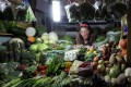 A vegetable vendor waits for customers at a market in Beijing as vegetable prices soar amid bad weather and poor transport. Photo: AP