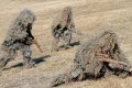 Camouflaged Japanese troops take part in a military drill. Photo: AP