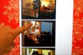 """In a posed picture, a person points to a website that features examples from photographer Michael Wolf's """"Window Watching"""" series."""