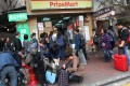 People gather outside a popular PrizeMart store in Mong Kok, with some queuing to buy their goods while others pack up their loot. Photo: David Wong