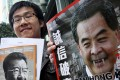 Raphael Wong Ho-ming with photos of Lew Mon-hung, left, and Leung Chun-ying, right, before entering the ICAC headquarters in North Point on Wednesday.  Photo: David Wong
