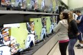 Shoppers eye televisions in a Caracas store ahead of a devaluation of the currency which sparked panic-buying. Photo: AFP