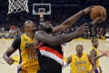 Los Angeles Lakers centre Dwight Howard, left, blocks the shot of Portland Trail Blazers centre J.J. Hickson as guard Kobe Bryant (second from right) and forward Earl Clark (right) look on. Photo: AP