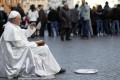 A street actor performs as the late Pope John Paul II at Piazza Navona in Rome. Photo: Reuters