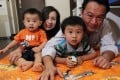 Happy father Ivan Wong and his wife, Shelley Lo, with their sons at home in Kowloon City. Thanks to new company policy, Ivan was able to enjoy paternity leave when they gave birth to their children. Photo: Edmond So