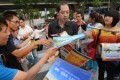 A man receives property development sales brochures from touts in Beijing.