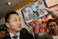Roy Tang, the director of broadcasting, meets media at RTHK headquarters in Kowloon Tong where a protester shows a picture of him in a Hitler outfit. He is accused of editorial interference. Photo: Sam Tsang