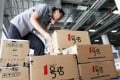 An employee packages items into boxes to fill orders at the Yihaodian (The Store) warehouse in Shanghai. Photo: Bloomberg