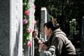 """A Chinese woman tends to a grave of a family member at a cemetary on """"Qingming"""" in Beijing. Photo: AFP"""