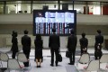 Spectators look at stock prices at the Tokyo Stock Exchange on Friday. The market gained 1.6 per cent at the close after earlier jumping about five per cent. Photo: AP