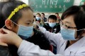 A teacher at an elementary school in Jinan, capital of Shandong province, instructs a pupil yesterday on the proper way to wear a mask. The elementary school was offering a class on how to prevent bird flu as health authorities on the mainland took more steps to cope with an increasing number of H7N9 bird flu cases. Photo: Xinhua