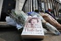 A book and floral tributes are left in honour of former British Prime Minister Margaret Thatcher outside her home in central London. Photo: AFP
