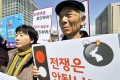 """South Korean activists hold placards reading """"We oppose war!"""" during an anti-war rally urging peace talks with North Korea in Seoul on Tuesday. Photo: AFP"""