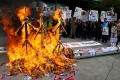 South Korean activists burn effigies of North Korea's founder, the late Kim Il-sung, late leader Kim Jong-il and leader Kim Jong-un during a rally in Seoul on Monday. Photo: EPA