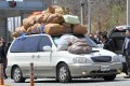 South Korean representatives of the business companies at Kaesong greet a car carrying sacks of clothes made in North Korea's Kaesong joint industrial complex on Wednesday. Photo: AFP
