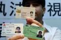 Tahir Khan displays his identity cards. Photo: Jonathan Wong