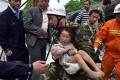A rescuer carries a child after she was pulled out from under the rubble of her home. The quake that struck yesterday has left at least 150 dead and 6,000 injured. Photo: AFP