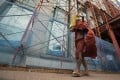 A Buddhist monk passes scaffolding of a construction site in downtown Yangon. Photo: EPA