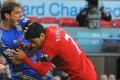 Luis Suarez bites the arm of Branislav Ivanovic. Photo: AFP