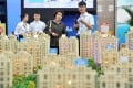 A visitor learns housing information in front of the model of a residential housing project during the 5th Western China House and Automobile Fair in Yinchuan. Photo: Xinhua