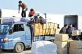 South Korean workers unload products made at the inter-Korean Kaesong Industrial Complex in North Korea, after the products arrived at at a military checkpoint in the border city of Paju, on Saturday. Photo: AFP