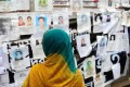 A relative looks at a board posting photos of the dead and missing workers from the factory that collapsed in Dhaka last week. Photo: AFP