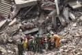 Workers try to release two bodies trapped in the rubble of a collapsed garment factory building near Dhaka, Bangladesh, on Tuesday. Photo: AP