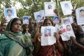 Relatives hold up portraits of missing family members from last week's collapse of a garment factory building in Savar. Photo: AP