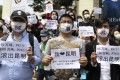 Residents wearing masks hold posters with slogans including 'PX get out of Kunming' as they protest against a planned refinery. Photo: Reuters