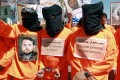 Yemenis wearing orange jumpsuits, similar to those worn by prisoners at the US detention centre in Guantanamo Bay, hold a protest demanding the release of inmates on hunger strike. Photo: AFP