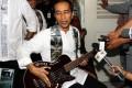 Joko Widodo with his bass guitar gift from Metallica. Photo: AFP