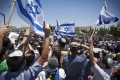Jewish settlers wave Israeli flags during a recent protest over the West Bank settlement of Beit El near Ramallah. Photo: AP