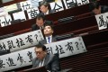 Pro-establishment lawmakers display banners denouncing the filibuster in Legco. Photo: K. Y. Cheng