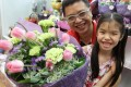 As crowds throng the shops on Flower Market Road in Mongkok, Tam Ka-fai helps his seven-year-old daughter Beatrice to buy a bouquet for her mother to celebrate Mother's Day, which falls today. Photo: Edward Wong