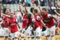 Arsenal players celebrate their victory after the final whistle in the English Premier League football match against Newcastle United, on Sunday. Photo: AFP