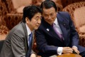 Finance Minister Taro Aso (right) and Prime Minister Shinzo Abe have been warned not to assume to assume that domestic investors will keep financing Japan's ballooning debt. Photo: AFP