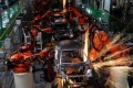 Robotic arms weld cars in a factory in Zhejiang province.