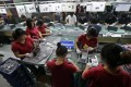 Employees work at a Foxconn factory in Wuhan, Hubei province. Photo: Reuters