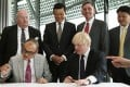London Mayor Boris Johnson and Advanced Business Parks Chairman Xu Weiping sign documents at City Hall in London. Photo: Reuters