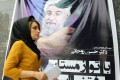 A young Iranian woman passes by a huge election poster of Iranian presidential candidate Hassan Rowhan for the upcoming June 14 for the upcoming election, in Tehran. Photo: EPA